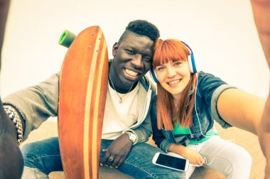 Hipster multiracial couple in love taking selfie on white background - Fun concept with alternative fashion and technology trends - Redhead girlfriend with afro american guy - Vintage filtered look