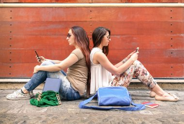 Hipster couple of girlfriends in disinterest moment with mobile smart phones - Concept of relationship apathy sadness and isolation using new technologies - Female friends with smartphones addiction