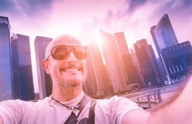 Handsome man taking selfie at modern urban area of Marina Bay in Singapore at sunset - Adventure travel lifestyle around south east Asia - Composition with tilted horizon and blue marsala color tones