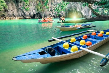 Longtail boats at cave entrance of Puerto Princesa subterranean underground river - Nature trip in Palawan exclusive Philippines destination - People with light equipment during adventurous excursion