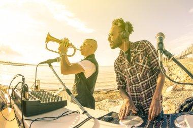 """Картина, постер, плакат, фотообои """"trendy hipster dj, играющий летние хиты на закате пляжной вечеринки с исполнителем трюмпета - концепция праздничного отдыха в клубе под открытым небом с местом для хаус-музыки - теплый винтажный фильтр для загара """", артикул 75655131"""