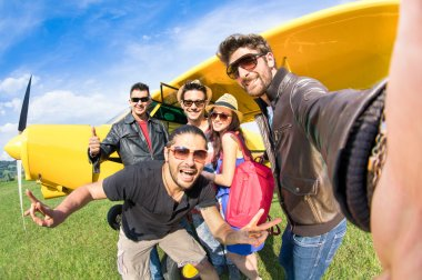 Best friends taking selfie at aeroclub with ultra light airplane - Happy friendship fun concept with young people and new technology trend - Sunny afternoon vivid color tones - Fisheye lens distortion