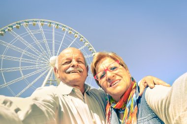 Happy retired senior couple taking selfie at travel around the world - Concept of active playful elderly with mobile phone - Mature people fun lifestyle in sunny day with strong sunlight color tones