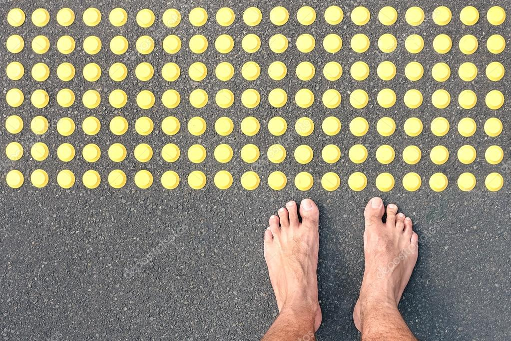 Naked Human Barefoot On Asphalt Road At Tactile Bumps Paving