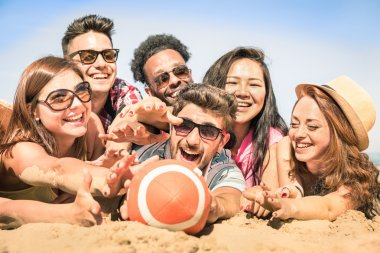 Group of multiracial happy friends having fun at beach games - International concept of summer joy and multi ethnic friendship together - Warm sunny afternoon color tones with shallow depth of field
