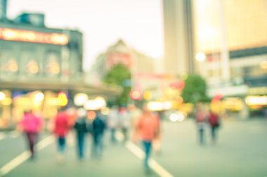 Blurred defocused background of people walking on the road with vintage multicolored filter - Abstract bokeh of crowded Queen Street in Auckland city center during rush hour in urban business area
