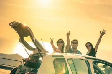 Best friends cheering by car road trip at sunset - Group of happy people outdoor on vacation tour - Friendship concept at travel with positive nostalgic emotions - Soft focus due to backlight contrast