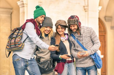 Group of young hipster tourists friends having fun with smartphone in the old town - Traveling lifestyle concept with happy people connected with new trendy technologies - Warm autumn filtered look