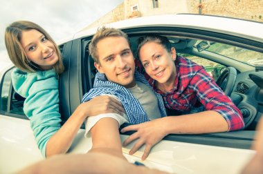 Handsome guy having fun with girlfriends - Best friends taking selfie at car trip on the road - Happy friendship and wanderlust concept with people traveling together - Soft vintage filtered look