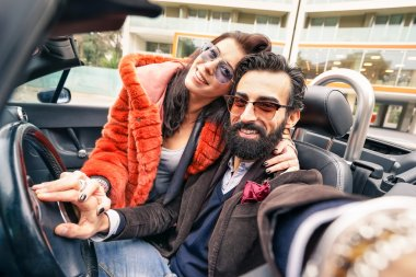 Handsome hipster boyfriend having fun with girlfriend - Happy couple taking selfie at car trip - Modern love relationship concept with people traveling together - Main focus on face of the guy