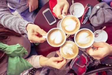 Group of friends drinking cappuccino at coffee bar restaurant - People hands cheering and toasting with upper view point - Social gathering concept with men and women - Vintage marsala filtered look