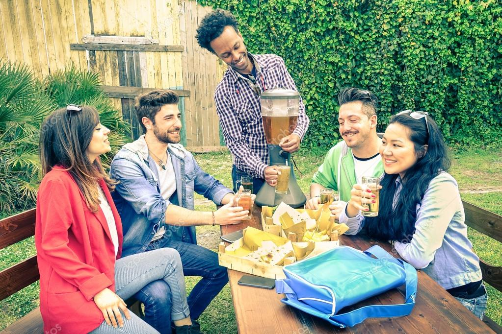 Multiracial group of happy friends eating and toasting at garden barbecue party - Concept of happiness with young people outdoors enjoying picnic food together - Vintage filtered look