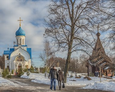 Moscow. Govorovo. January 19, 2015. New Church of the Nativity of the Blessed Virgin and the wooden church of Alexander Nevsky. People go for the baptismal water.
