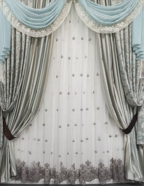 Interior design in a classic and luxurious style. Combined curtains, tulle and pelmet on the window.