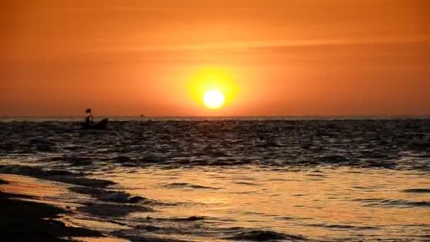 A strandon, este, és a naplementét hullám