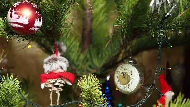 Vánoční sezóna, Nový rok. Vánoční ozdoby visí na vánočním stromečku obklopený barevnými světly. Detailní záběr.