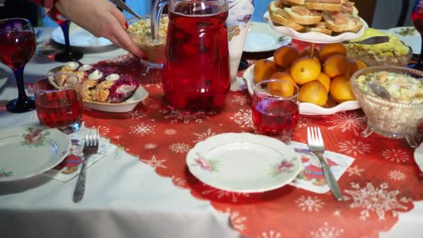 Holidays. Womens hands put prepared dishes on the festive table. Out of focus.