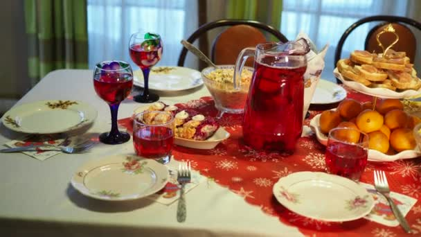 Holiday season. Table with various dishes and drinks, decorated for the holiday. Panning, Close-up shooting.