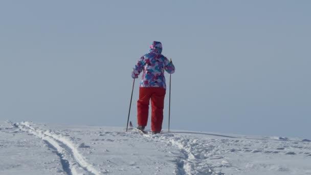 Jahreszeiten. Eine ältere Frau klettert auf Skiern auf einen schneebedeckten Hügel. Sibirien.