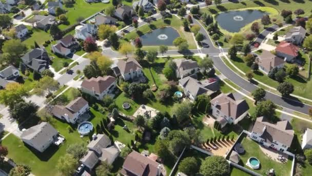 Overhead aerial view of colorful autumn trees, residential houses and yards with drainage pond along suburban street in Chicago area. Midwest USA. 4K