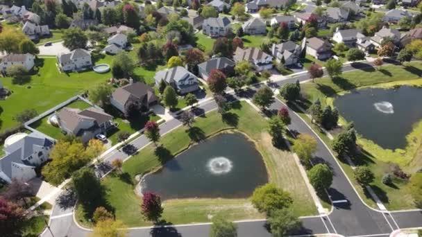Fölötti légi kilátás színes őszi fák, lakóházak és udvarok vízelvezető tó mentén kertvárosi utcában Chicago területén. Közép-Nyugat USA. 4K