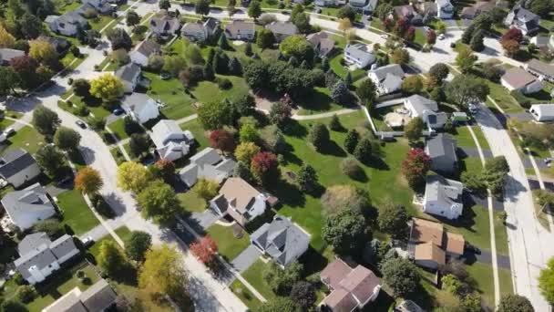 Fölötti légi kilátás színes őszi fák lakóházak és udvarok mentén kertvárosi utcában Chicago területén. Közép-Nyugat USA. 4K