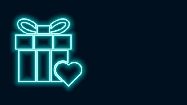 Ragyogó neon vonal Ajándék doboz és szív ikon elszigetelt fekete háttérrel. Valentin nap. 4K Videó mozgás grafikus animáció
