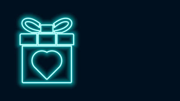 Ragyogó neon vonal Ajándék doboz és szív ikon elszigetelt fekete háttérrel. Március 8. Boldog Nők Nemzetközi Napja. 4K Videó mozgás grafikus animáció