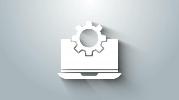 Fehér Laptop és fogaskerék ikon elszigetelt szürke háttér. Laptop szolgáltatás koncepció. Alkalmazás beállítása, beállítási lehetőségek, karbantartás, javítás, javítás. 4K Videó mozgás grafikus animáció