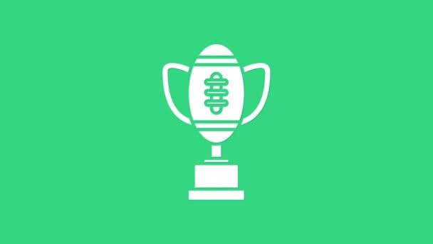 Bílý pohár a americký fotbalový míč ikona izolované na zeleném pozadí. Symbol vítězné trofeje. Mistrovství nebo soutěžní trofej. Grafická animace pohybu videa 4K