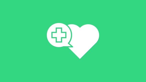 Fehér Szív egy kereszt ikon elszigetelt zöld alapon. Elsősegély. Egészségügyi, orvosi és gyógyszertári jelek. 4K Videó mozgás grafikus animáció