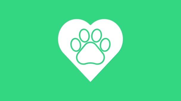 Fehér Szív állatokkal lábnyom ikon elszigetelt zöld alapon. Mancs a szívben. Szeretettel az állatoknak. 4K Videó mozgás grafikus animáció