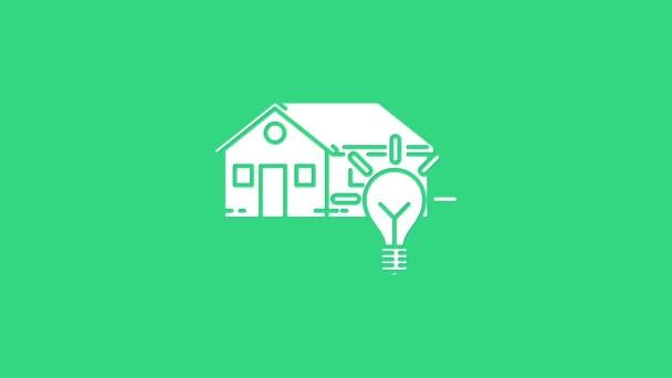 Bílý Chytrý dům a žárovka ikona izolované na zeleném pozadí. Grafická animace pohybu videa 4K