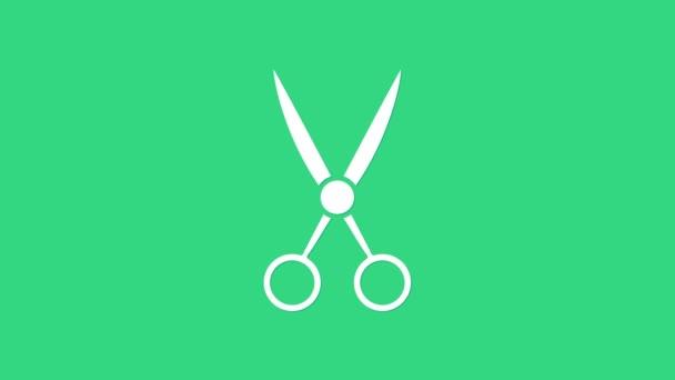 Fehér olló fodrász ikon elszigetelt zöld alapon. Fodrász, divatszalon és borbély felirat. Borbélyüzlet szimbólum. 4K Videó mozgás grafikus animáció