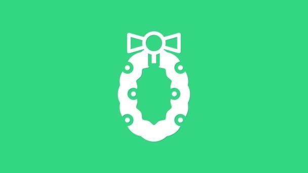 Bílé vánoční věnec ikona izolované na zeleném pozadí. Veselé Vánoce a šťastný nový rok. Grafická animace pohybu videa 4K