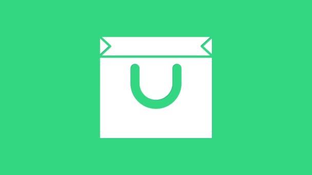 Fehér Bevásárlótáska ikon elszigetelt zöld háttérrel. Bevásárlótáska bolt szerelem, mint a szív ikon. Valentin-napi szimbólum. 4K Videó mozgás grafikus animáció