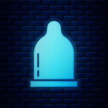 Glowing neon Condom icon isolated on brick wall background. Safe love symbol. Contraceptive method for male.  Vector. icon