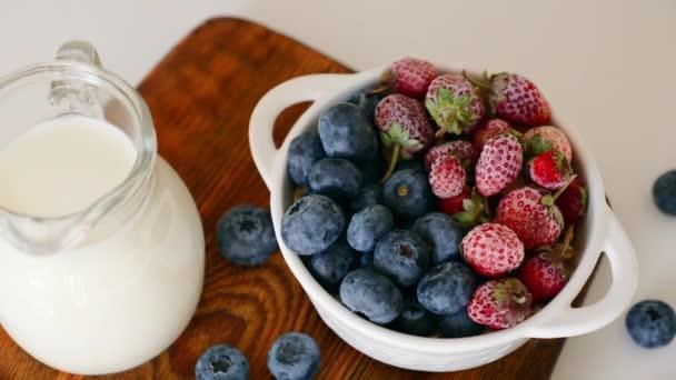Snídaňový pohár s borůvkami a jahodami, džbán s mlékem na stole