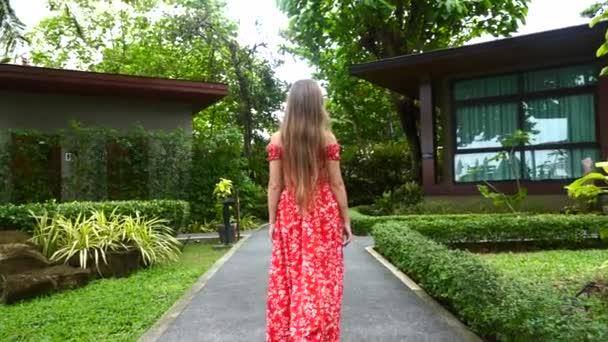 Wanderin im roten Kleid geht barfuß auf Pfaden im modernen Tropical Resort