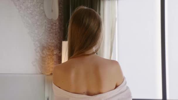 Back View of Sensual Woman in Bathrobe Standing Near Window in Luxury Hotel