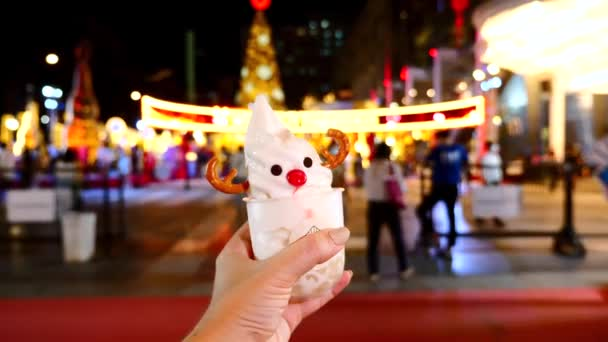 Weihnachtliches Eis auf dem Neujahrsmarkt. Frau hält lustigen gefrorenen Joghurt in der Hand