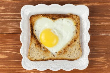 Slice of cereal toast bread with cut out heart shape full egg on white plate