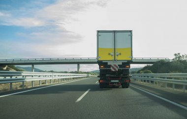 Heavy tow truck carrying semi-trailer truck on freeway. Truck Height Restrictions and Bridge Clearance concept