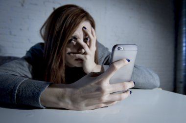 young sad vulnerable girl using mobile phone scared and desperate suffering online abuse cyberbullying