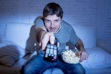 man at home lying on couch at living room watching tv eating popcorn bowl using remote control