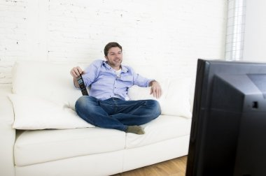 young happy man watching television smiling and laughing in sofa
