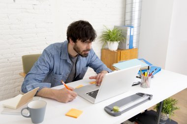 young hispanic hipster businessman working at computer home office