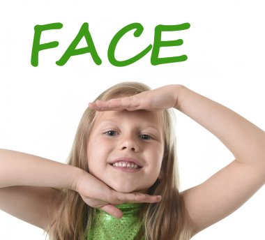 Cute little girl showing face in body parts learning English words at school