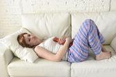 Fotografie junge Frau hält Wärmflasche im schmerzenden Bauch und leidet unter Magenkrämpfen