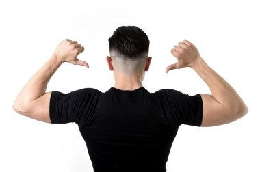 attractive sport man pointing on his black t-shirt with  copy sp